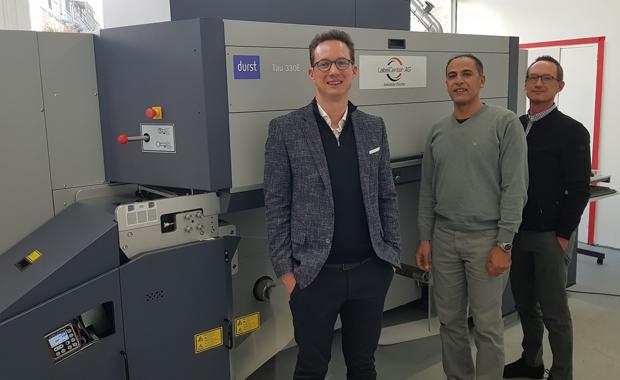 Der Inhaber von Label Center Hossam Elgendy (Mitte) zusammen mit Christian Salhofer (li.) und Patrick Salhofer vom Vertriebsunternehmen Jetpack vor der neuen Tau 330 E von Durst.
