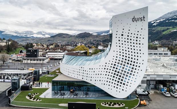 Durst hat seine neue Firmenzentrale in Brixen eröffnet. Das futuristische Gebäude soll den Wandel des Unternehmens hin zu einem hochintegrierten Prozess-Dienstleister symbolisieren.