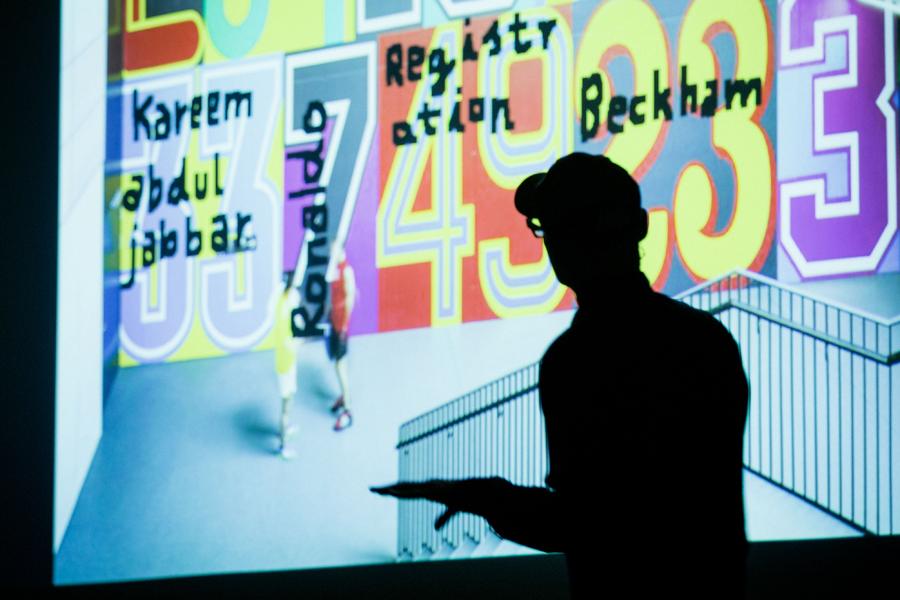 """Schattenmann auf der Tÿpo St. Gallen: Andreas Uebele setzte den furiosen Schlusspunkt, im Hintergrund: Blick auf farbenfrohe """"Wohlfühlwandbilder"""" mit Zahlen-Buchstaben-Ornamentik aus der Welt des Sports fürs Adidas-Fitnessstudio."""