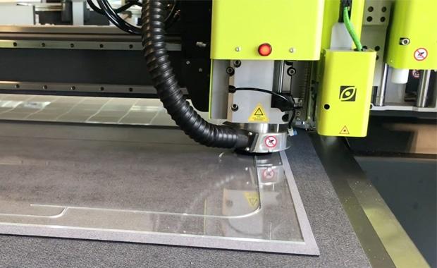 Druckindustrie: Kongsberg-Schneidetisch bei der Produktion einer Niesschutzwand aus Acrylglas.
